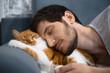 Leinwanddruck Bild - Sleeping young man and red white cat.