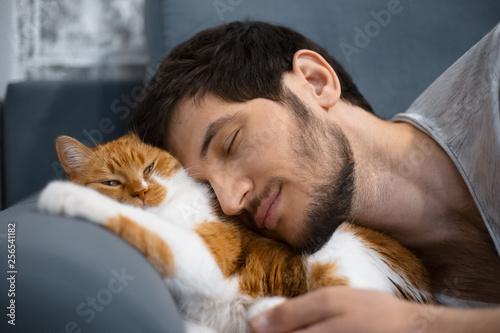 Leinwanddruck Bild Sleeping young man and red white cat.