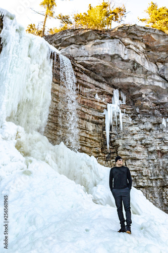 Man exploring mountain with snow and a frozen waterfall  © Michele