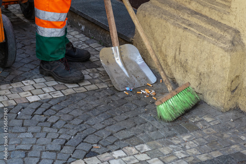Street cleaning. A janitor sweeps cigarette butts in the street.