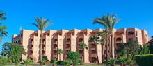 """Постер, картина, фотообои """"Palm trees and tropical vegetation growing in courtyard of resort"""""""
