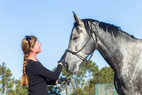 Woman and her  horse training affection feeding countryside equestrian sand arena blue sky afternoon sport lifestyles.