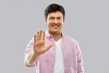 gesture and people concept - smiling young man showing his palm over grey background - 256611158