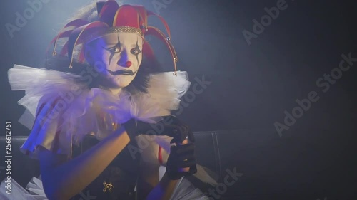 Frowning clown woman with white and black old makeup and a red hat, slow motion