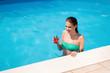 Beautiful young woman enjoying summer vacation in pool