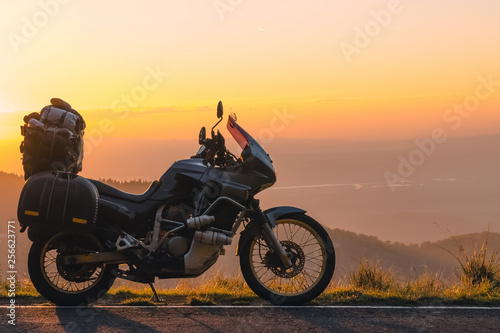 Adventure motorcycle, silhouette touristic motorbike. the mountain peaks in the dark colors of the sunset. Copy space. Concept of Tourism, adventures, active lifestyle, Transfagarasan, Romania
