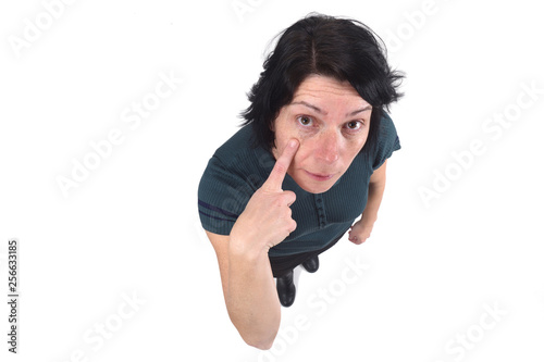 woman with finger on eye on white