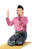 Portrait of young and handsome asian man with traditional clothing rising hand for pray over white background