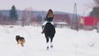 A woman riding a horse in a village with a dog running near by them