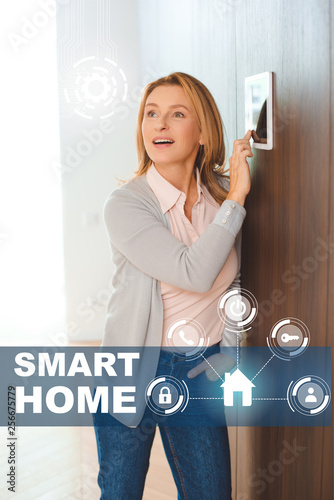 happy inspired woman using smart house control panel