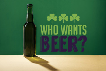 glass beer bottle near who wants beer lettering on green background