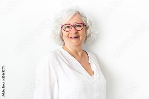 Leinwanddruck Bild A Senior woman studio isolated on grey wall laughing cheerful
