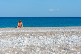 Young woman sitting on beautiful pebble beach