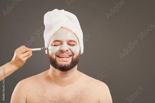 Leinwanddruck Bild A funny man in a face mask in a beauty salon.