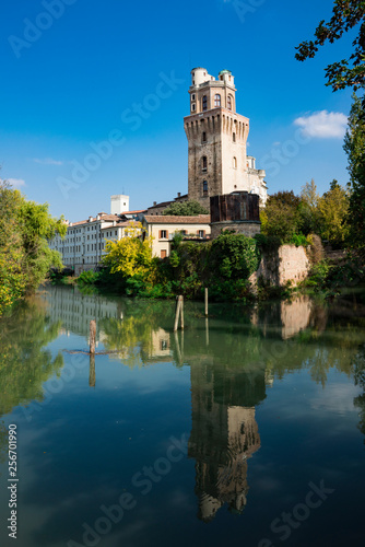 Foto Murales tower of Astronomical Observatory of Padua, Italy, along the river., with reflection