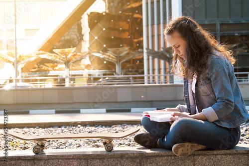 schoolgirl reading a book on street in big city