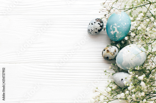 Happy Easter. Stylish Easter eggs with spring flowers border, flat lay on white wooden background with space for text. Modern easter eggs painted with natural dye in blue and grey marble. - 256727902