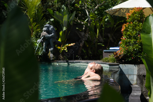 Leinwanddruck Bild Sensual young woman relaxing in outdoor spa infinity swimming pool surrounded with lush tropical greenery of Ubud, Bali. Wellness, natural beauty and body care concept.