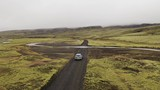 Aerial drone shot of SUV crossing a river ford in Highlands of Iceland