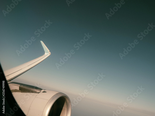 Pale colored film effect over view from window of plane turbine in flight high above clouds insunlight - 256749998