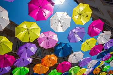 Street art consisting of multi coloured umbrella's in Arles, France