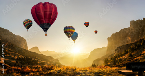 Leinwandbild Motiv Beautiful panoramic nature landscape of countryside mountains with colorful high hot air balloons festival in summer sky. Vacation travel panorama background.