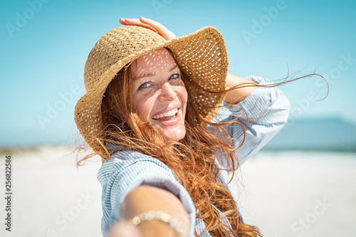 Leinwandbild Motiv Smiling mature woman with straw hat