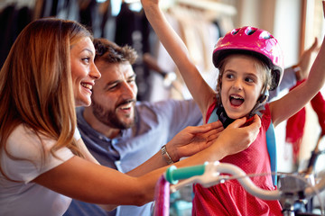 Family buying new bicycle for little girl in bike shop .