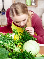 Woman in kitchen having many green vegetables