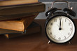 piles of different old books on a dusty table and an alarm clock