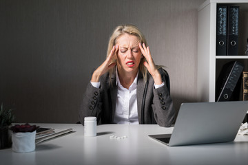 Woman feeling headache at work © Kaspars Grinvalds
