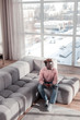 Kind stylish freelancer sitting on cozy sofa
