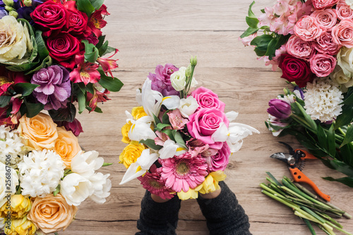Partial view of florist holding bouquet of fresh flowers on wooden surface - 256867506