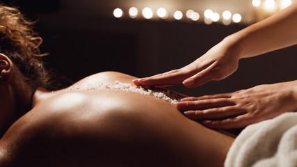 Salt scrub massage. Woman relaxing in health spa © Prostock-studio