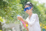 thai girl playing water splashing in song kran festival thailand new year concept