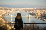 Young woman is looking at the Chain bridge, Budapest parliament and cityscape from The Citadella which is a fortification located upon the top of Gellert Hill in Budapest, Hungary.