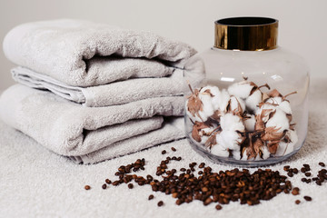 Top view spa and wellness setting with towels, natural cotton flowers in big pot and coffee beans for anticellulite massage for perfect healthy body and skin. Beauty luxury spa concept. Copyspace © ANR Production