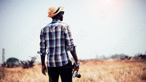 African man photographer holding camera on a dry field.16:9 style