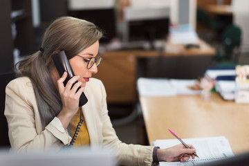 Attractive 30s woman working at office with telephone