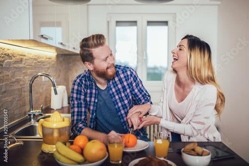 Leinwandbild Motiv Happy couple make orange juice in morning kitchen and having a good time.