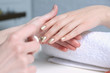 Leinwandbild Motiv Manicurist painting client's nails with polish in salon, closeup
