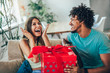 Quadro Man giving a surprise gift to woman at home