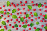 Fresh raspberries and mint leaves patterned over wooden background