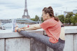 woman jogger not far from Eiffel tower stretching