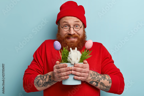 Leinwandbild Motiv Headshot of ginger positive young man with thick beard holds white fluffy decorative bunny and painted Easter eggs, wears red fashionable clothes, has holiday preparation, giggles happily indoor