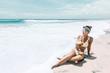 Leinwandbild Motiv Woman drinking coconut on the tropical beach