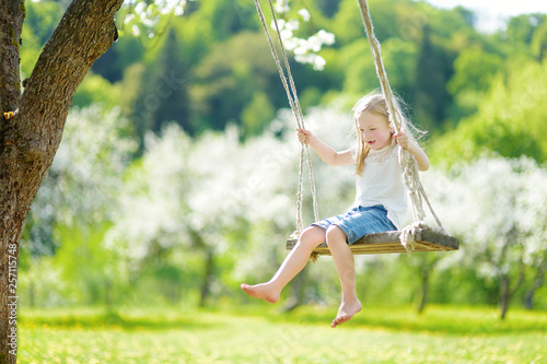 Leinwandbild Motiv Cute little girl having fun on a swing in blossoming old apple tree garden outdoors on sunny spring day.