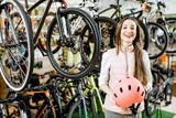 Portret młodej kobiety pozycja z sporta hełmem przy sklepem z bicyklami na tle