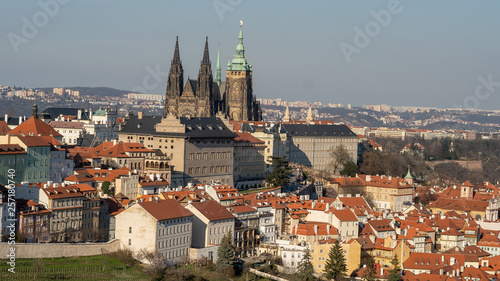 A beautiful spring view of Prague at sunrise from Petrin hill. Prague Castle and St. Vitus Cathedral on the left and a golden rising sun in the background - 257180740