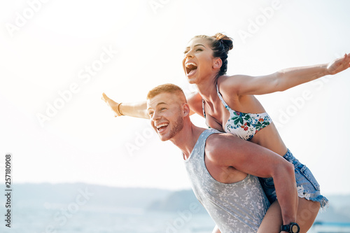 Leinwandbild Motiv Woman with arms outstretched enjoying piggyback ride,Woman with arms outstretched enjoying piggyback ride